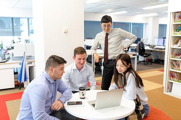 Staff working around a laptop